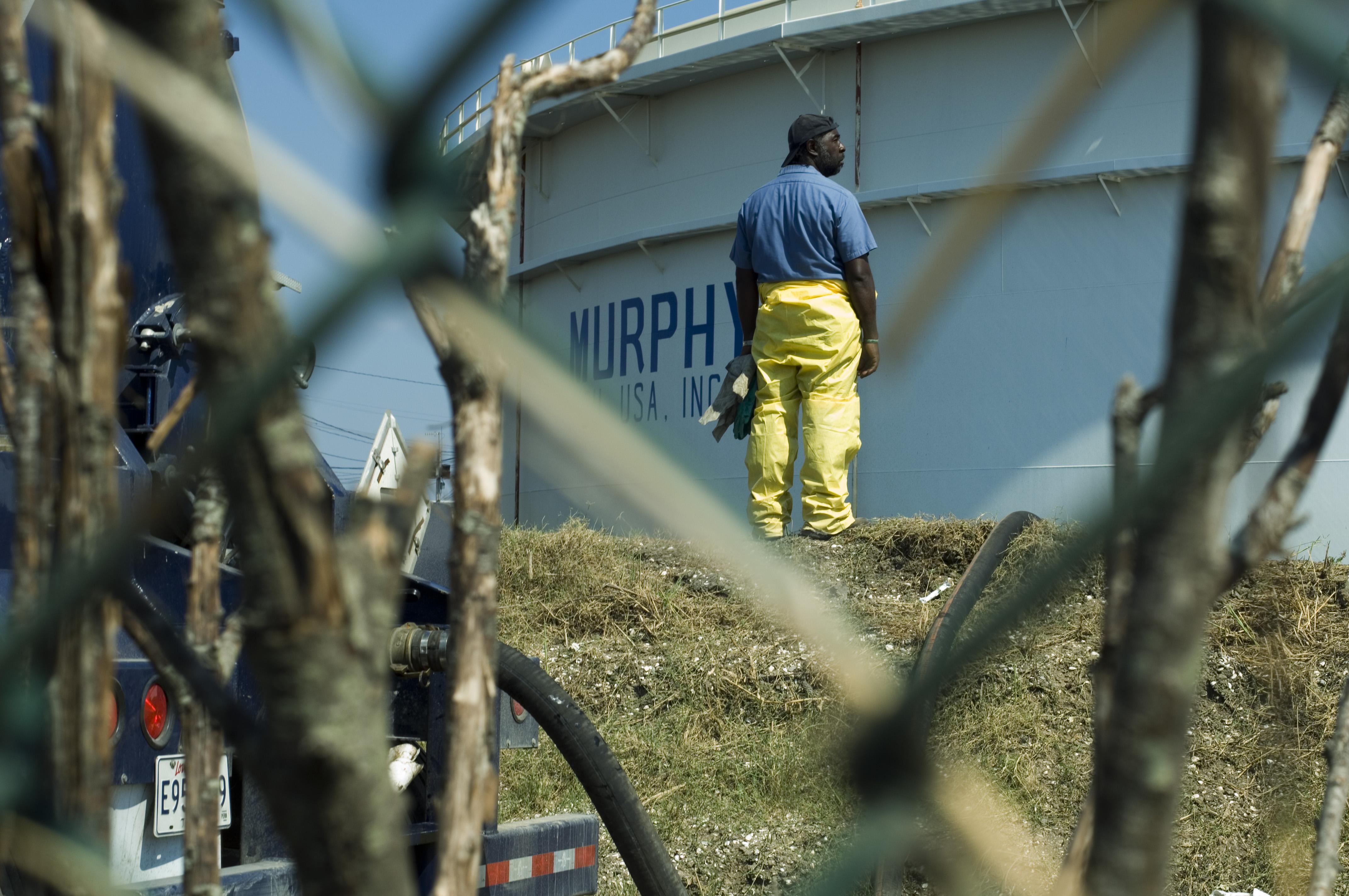 W rafinerii naftowej Murphy po huraganie Katrina: Do rafinerii przybywają jednostki ratownicze w celu usunięcia skutków wycieku ropy. Rafineria nie podała ilości rozlanej ropy, lecz według Straży Granicznej USA ze zbiornika wyciekło 1.072.500 galonów (1 galon = 3,785 l). Duża część tej ropy zalała tereny zamieszkałe wokół rafinerii, przekształcając je w obszary nie nadające się do zamieszkania. Według mieszkańców, prawnicy pracujący dla rafinerii dążą do kupna ich domów, aby powiększyć rafinerię i postawić magazyn zbiornikowy na ich ziemi. Foto: © Greenpeace / Christian Aslund